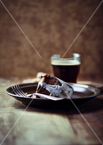 A slice of a marble cake with chocolate glaze