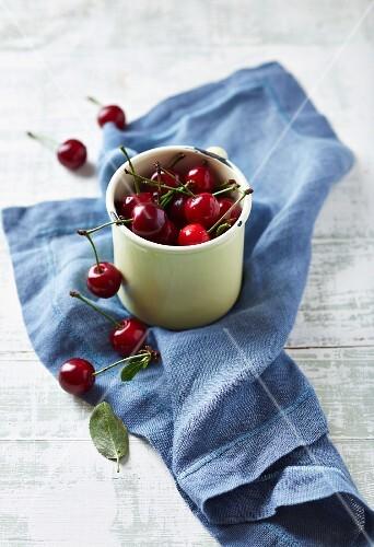 Sour cherries in an enamel mug