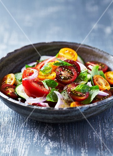 Summer salad with tomatoes, herbs, cucumber and red onion