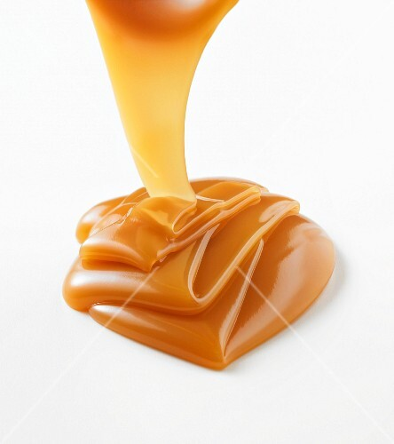Caramel sauce being poured onto a white surface