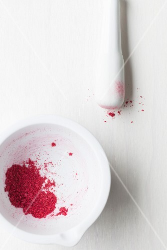 Crushed dried raspberries in a white mortar with a pestle