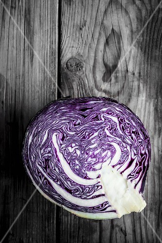 Half a red cabbage on a wooden surface
