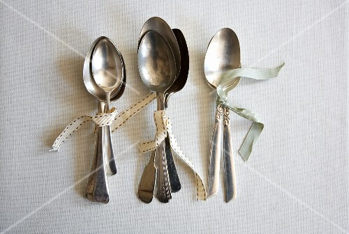 Various silver spoons tied together with ribbon