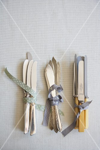 Bunches of various silver knives tied with ribbons