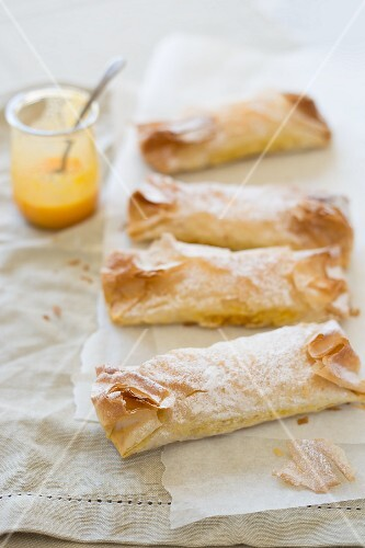 Pastéis de Tentugal (pudding-filled pastry rolls, Portugal) on parchment paper