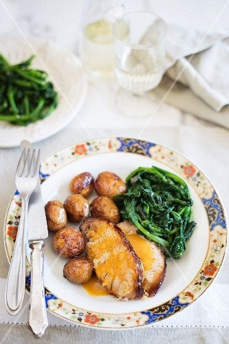 Roast piglet with potatoes and spinach