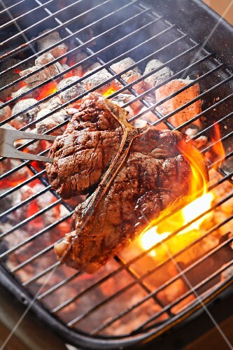 A T-bone steak on charcoal grill