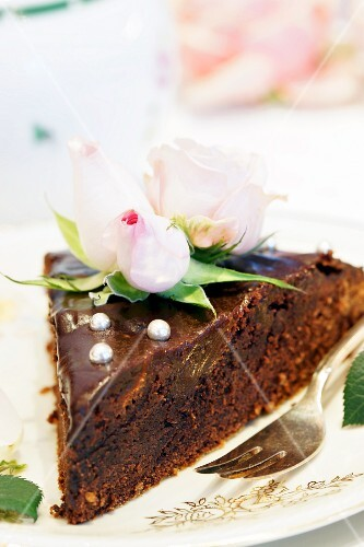 A sliced of chocolate cake decorated with roses