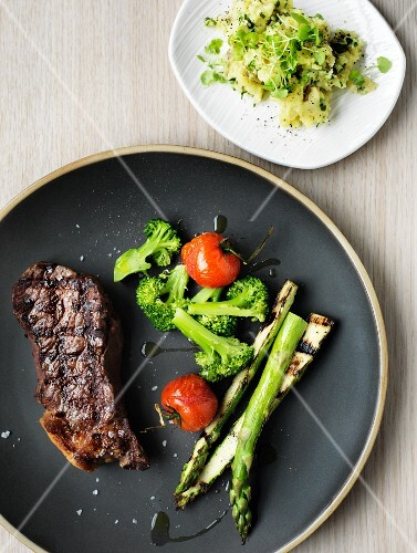 Beef steak with grilled asparagus and potato salad