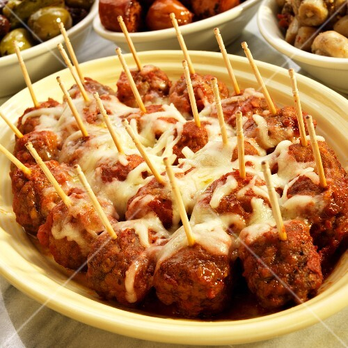 Meat balls in a spicy tomato sauce topped with melted cheese (Spain)