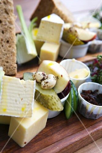 A cheese platter featuring pickled vegetables, fruit and bread