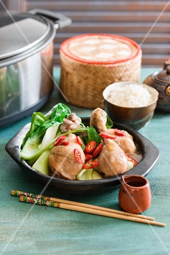 Spicy braised chicken with ginger and soy sauce served with bok choy and rice