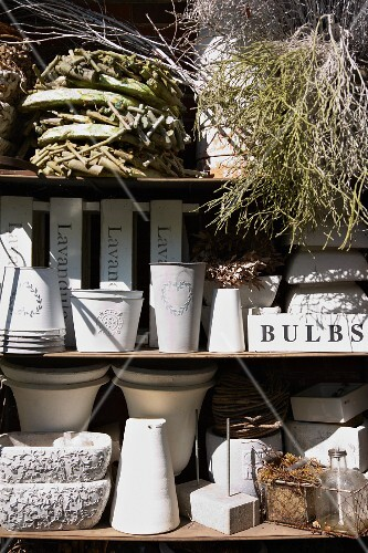 Stacks of woven and white-painted metal plant pots on a shelf