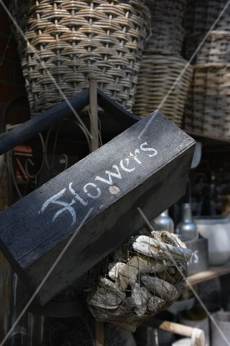 An old wooden basket with a label and a stack of wicker baskets