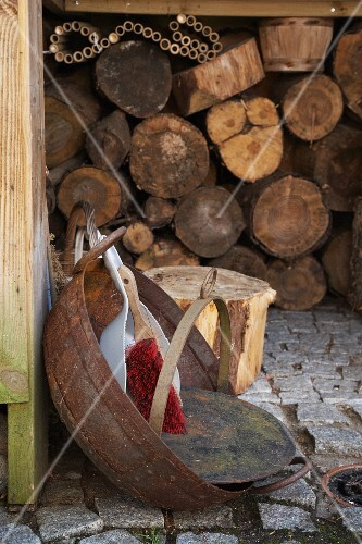 A dustpan and brush in a rusty bowl on cobbles in front of a wood shed