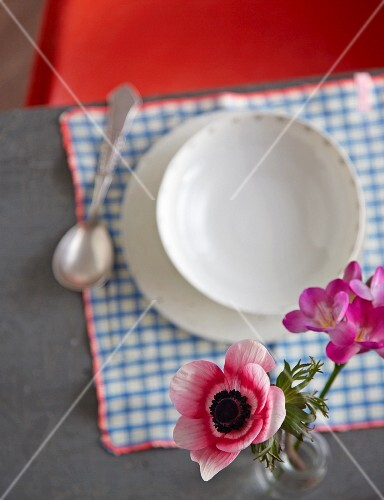 A view of a place setting with a soup bowl and flowers in a vase