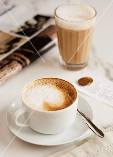 A cappucino and a caffe latte next to a magazine