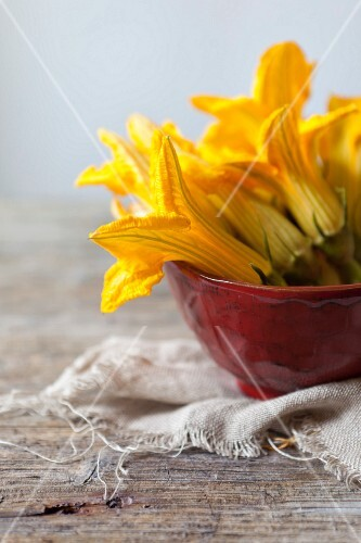 Courgette flowers in a red bowl on a rustic wooden table