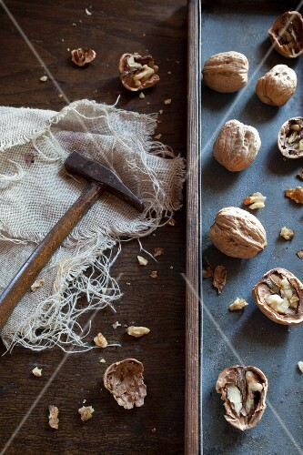 Walnuts an d a hammer on a rustic surface