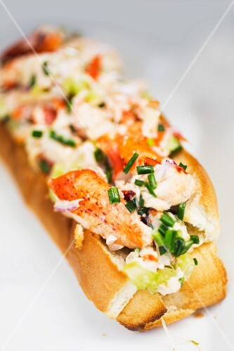 A slice of baguette topped with lobster and chives