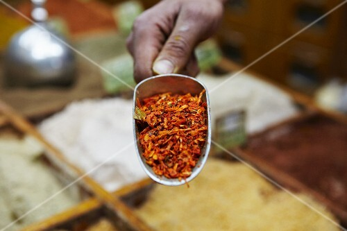 A hand holding a scoop of kabseh spice mix at a market