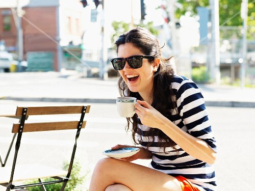 A young woman drinking coffee in a street cafe