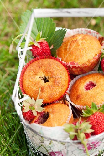Strawberry muffins in a wire basket in a meadow