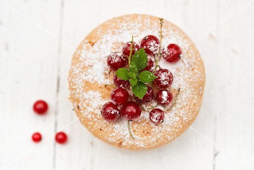 A mini cake with redcurrants and icing sugar