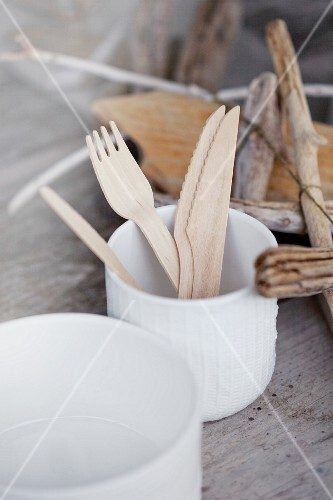 Wooden cutlery in a porcelain cup on a rustic wooden table