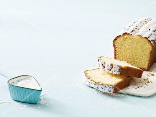 A sliced Madeira cake with icing sugar