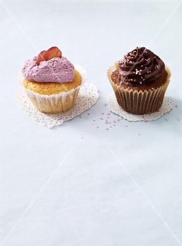 A grape cupcake and a chocolate cupcake