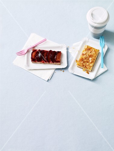 Two slices of tray bake cake on paper plates