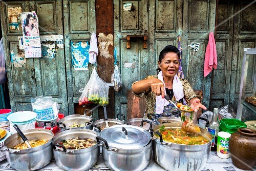 A woman ladling soup at a market stall, Thailand