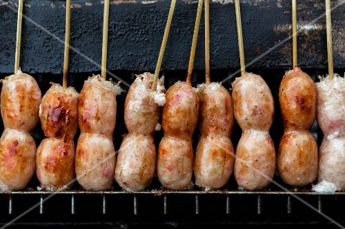 Sausages on sticks on a grill, Bangkok