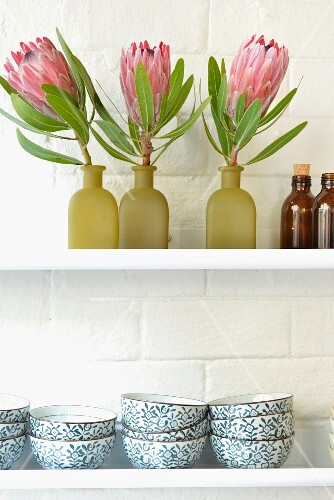 Decorative flowers and bowls on a wall shelf