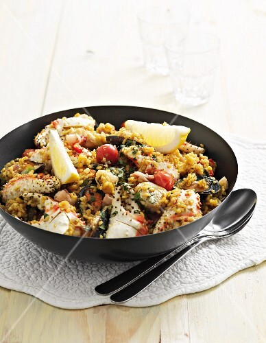 Paella with chicken, fish and tomatoes