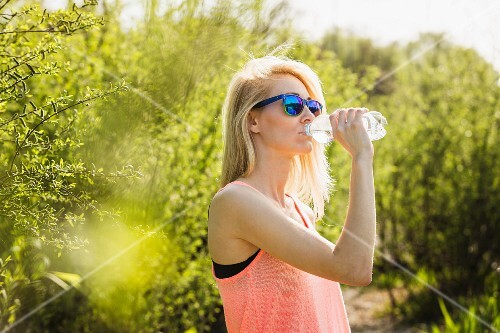 A young woman in a park drinking a bottle of water