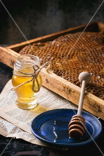A jar of honey with honeycombs