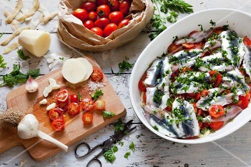 Sardine bake with potatoes, garlic, cherry tomatoes and parsley