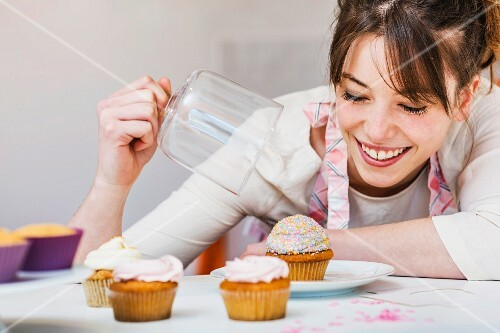 A woman in a kitchen with cupcakes and a glass cloche
