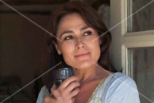 A middle-aged woman holding a glass of water