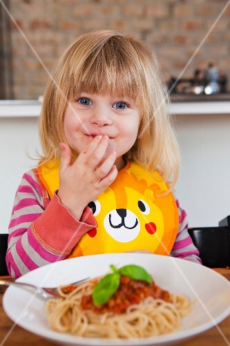 A little blonde girl eating spaghetti with her fingers