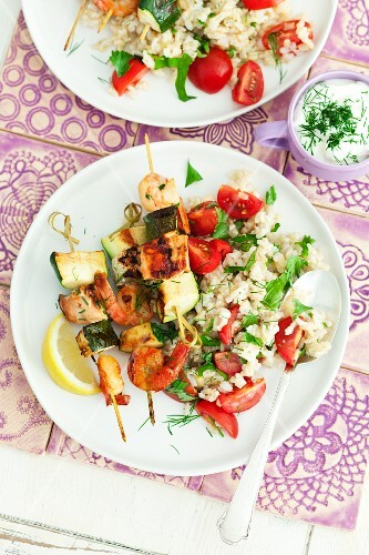 Salmon courgette skewers with prawns served with tomatoes and rice salad