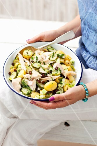A woman holding a bowl of potato salad with gherkins, raisins and smoked trout