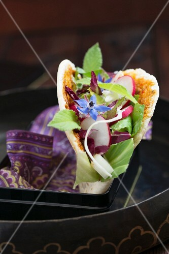A pita bread filled with a mixed leaf salad, radishes and borage flowers