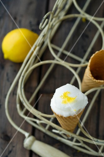 A scoop of lemon sorbet in an ice cream cone in a cone holder