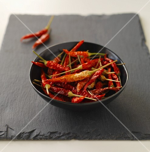 Dried red chillis in a black bowl