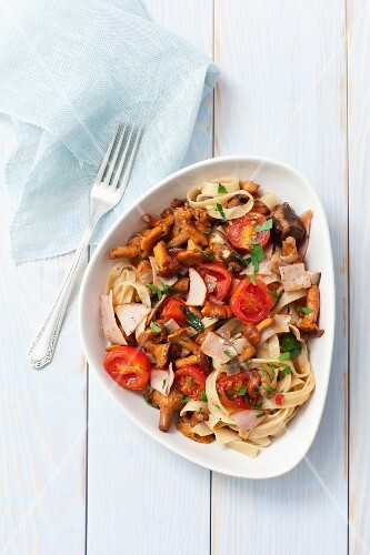 Tagliatelle with chanterelle mushrooms, ham and tomatoes
