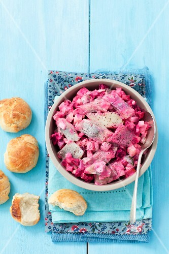 Herring salad with beetroot and egg served with homemade bread rolls