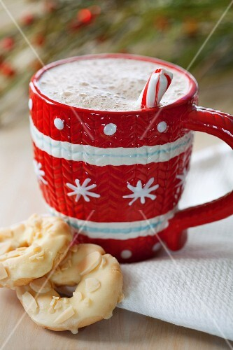 Hot chocolate in a red and white cup served with white chocolate biscuits